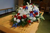 Mixed bunch of flowers sitting on a table in the middle of the church