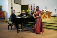 Margaret looking stunning in a claret dress leaning on the grand piano with Jonathan sitting at the ready